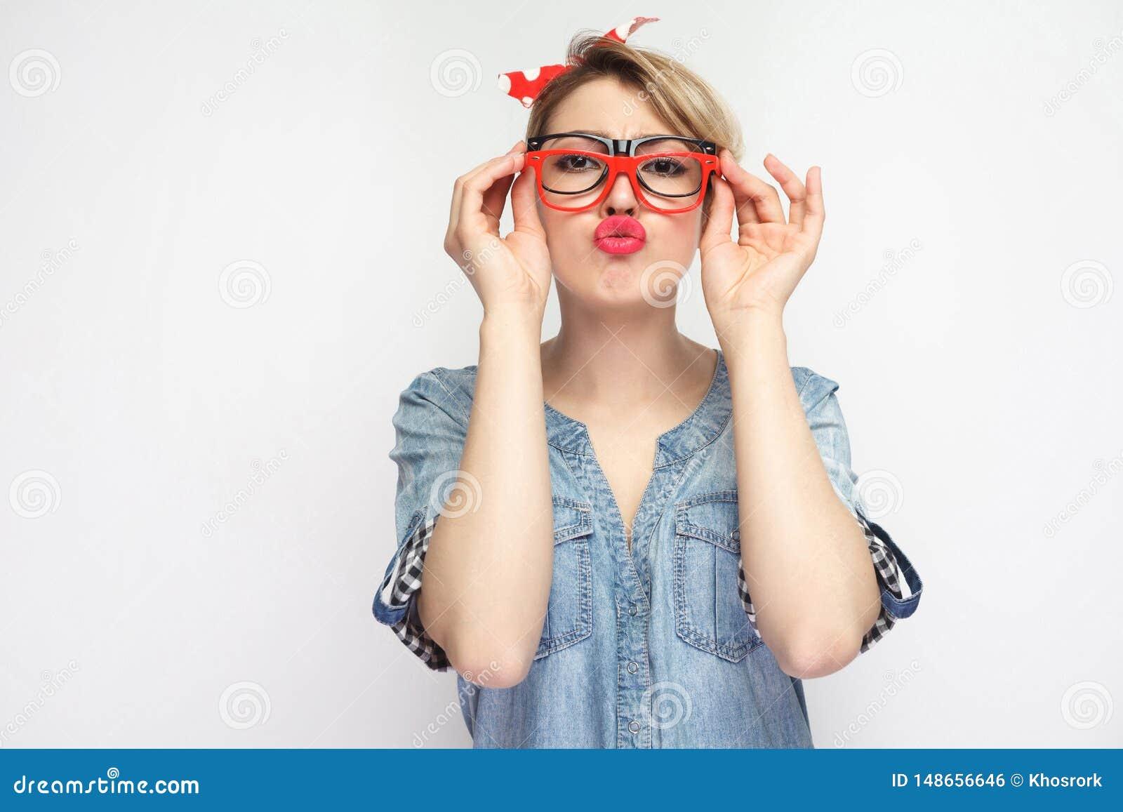 Retrato de la chica joven divertida en camisa azul casual del dril de algod?n con el maquillaje, situaci?n roja de la venda, inte
