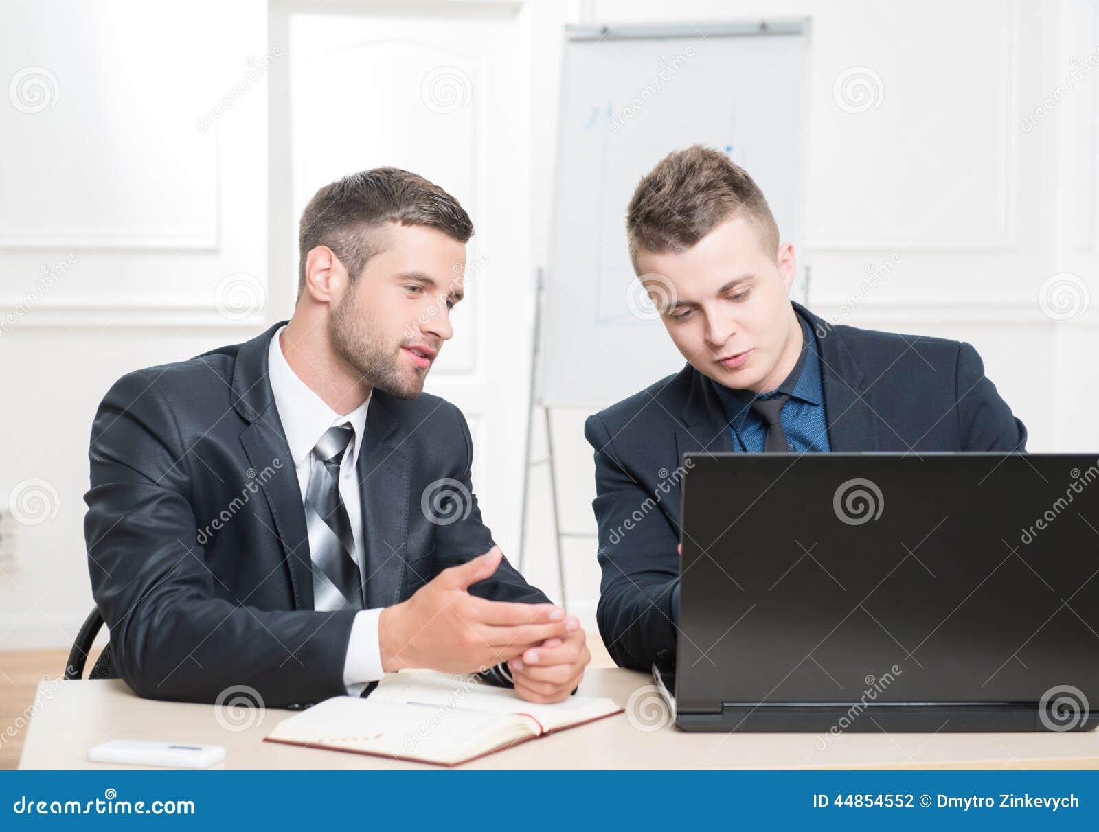 Retrato de la cintura-para arriba de dos hombres de negocios hermosos adentro