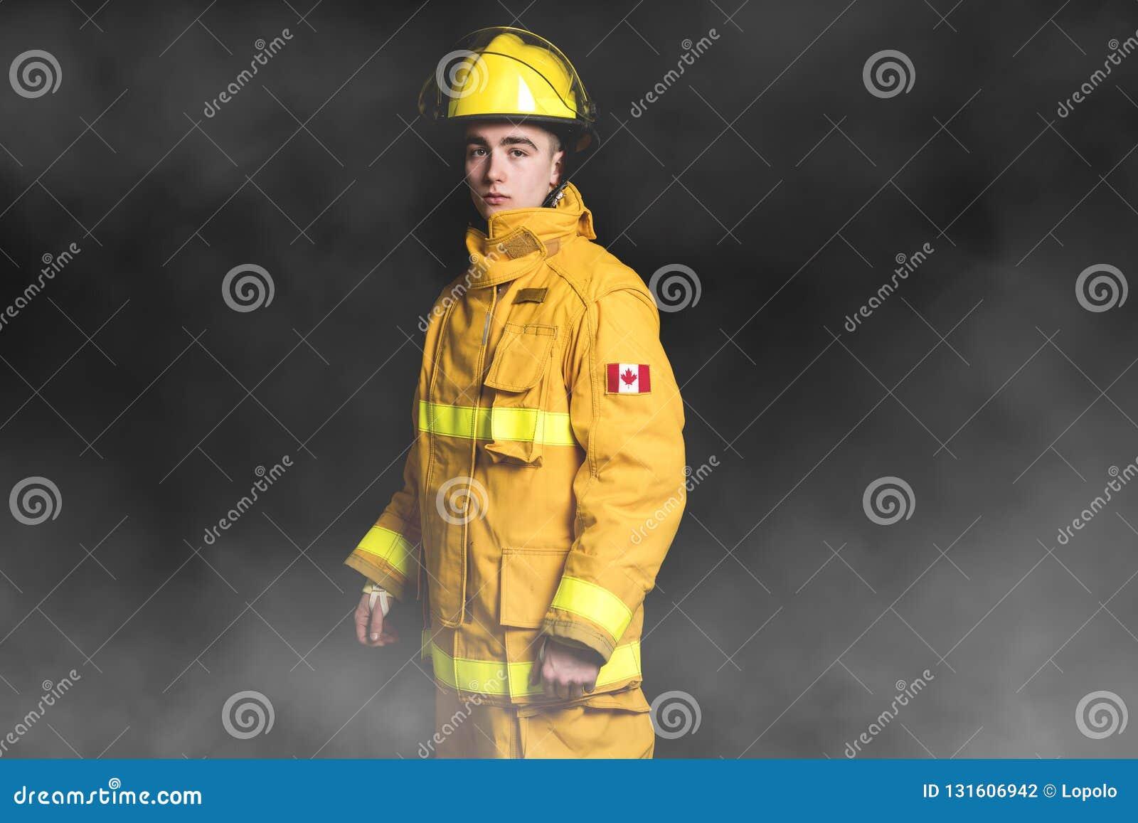Retrato de la cintura de la situación del bombero encima del tiro del estudio en fondo y moke negros