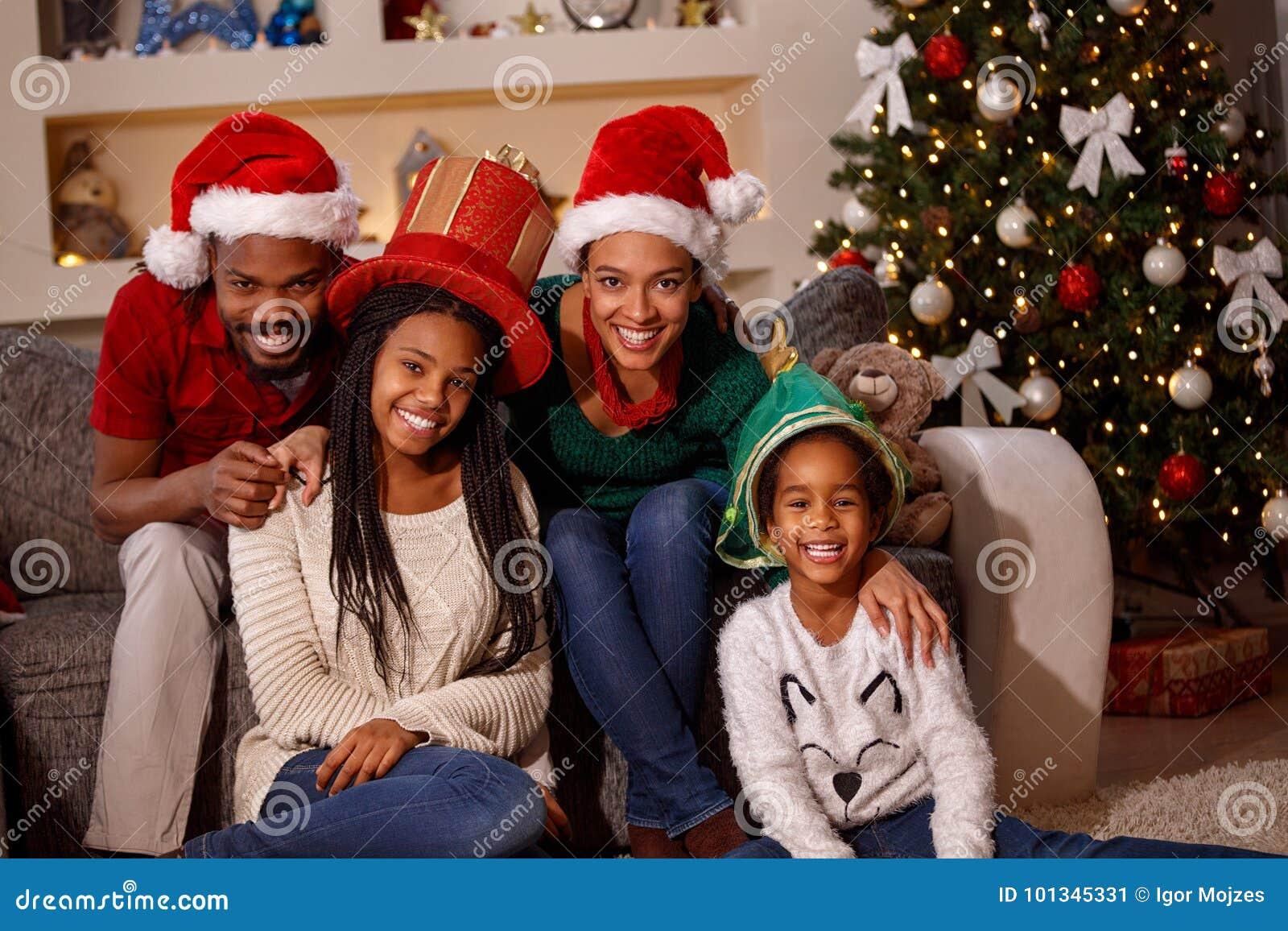 Retrato de la familia afroamericana en los sombreros de Papá Noel en la Navidad