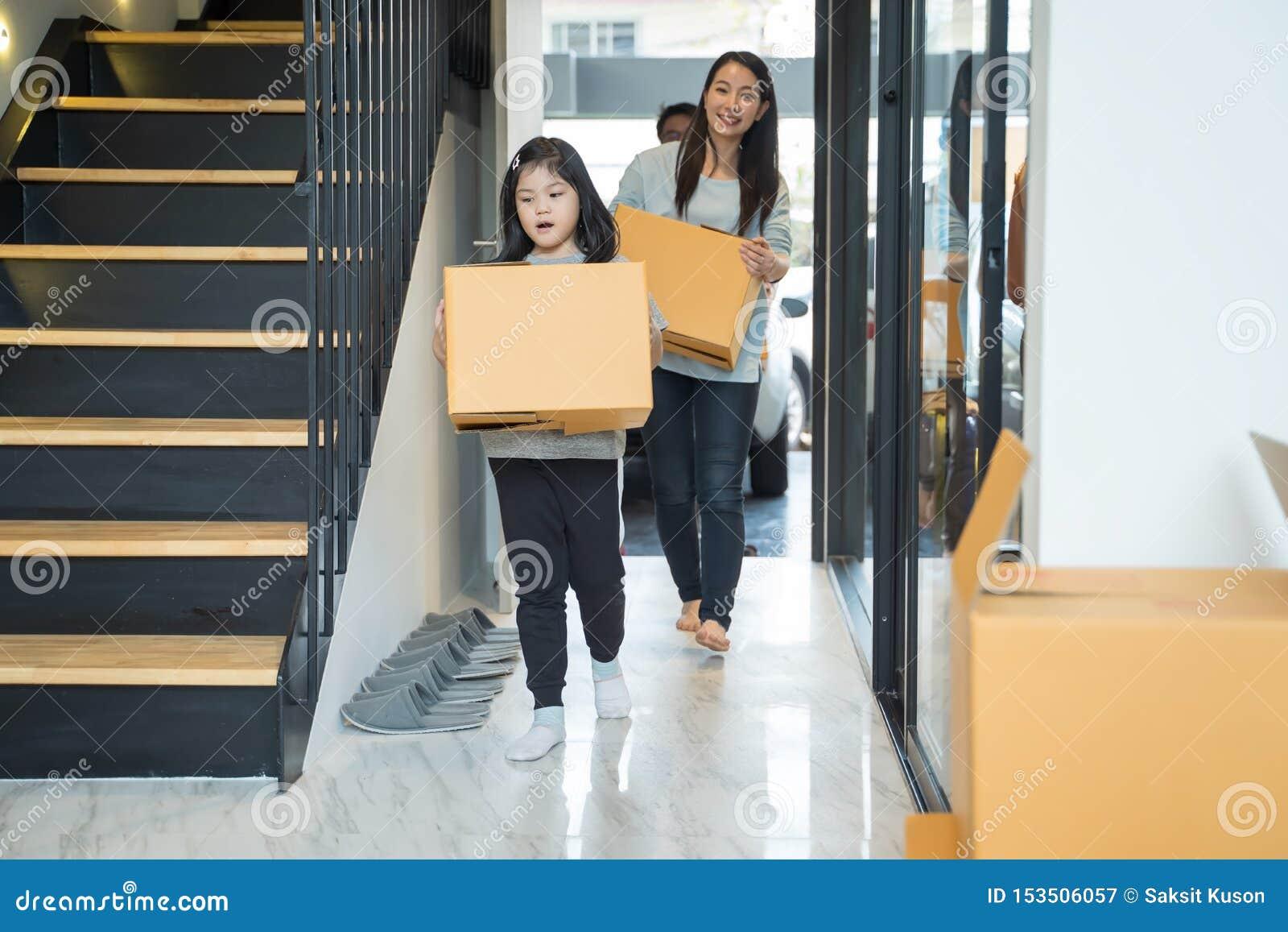 Retrato de la familia asiática feliz que se mueve a la nueva casa con las cajas de cartón