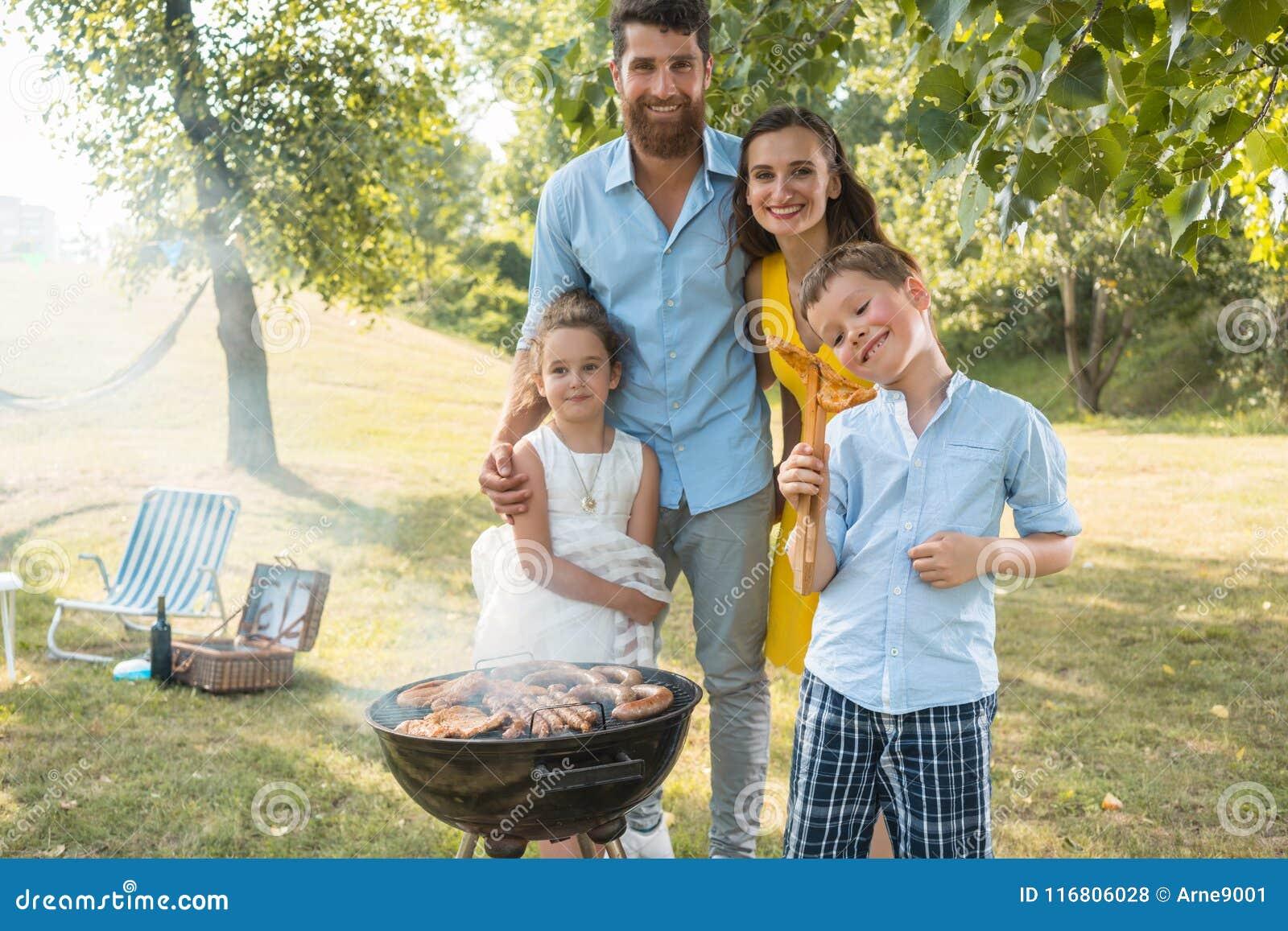 Retrato de la familia feliz con dos niños que se colocan al aire libre cerca de una barbacoa