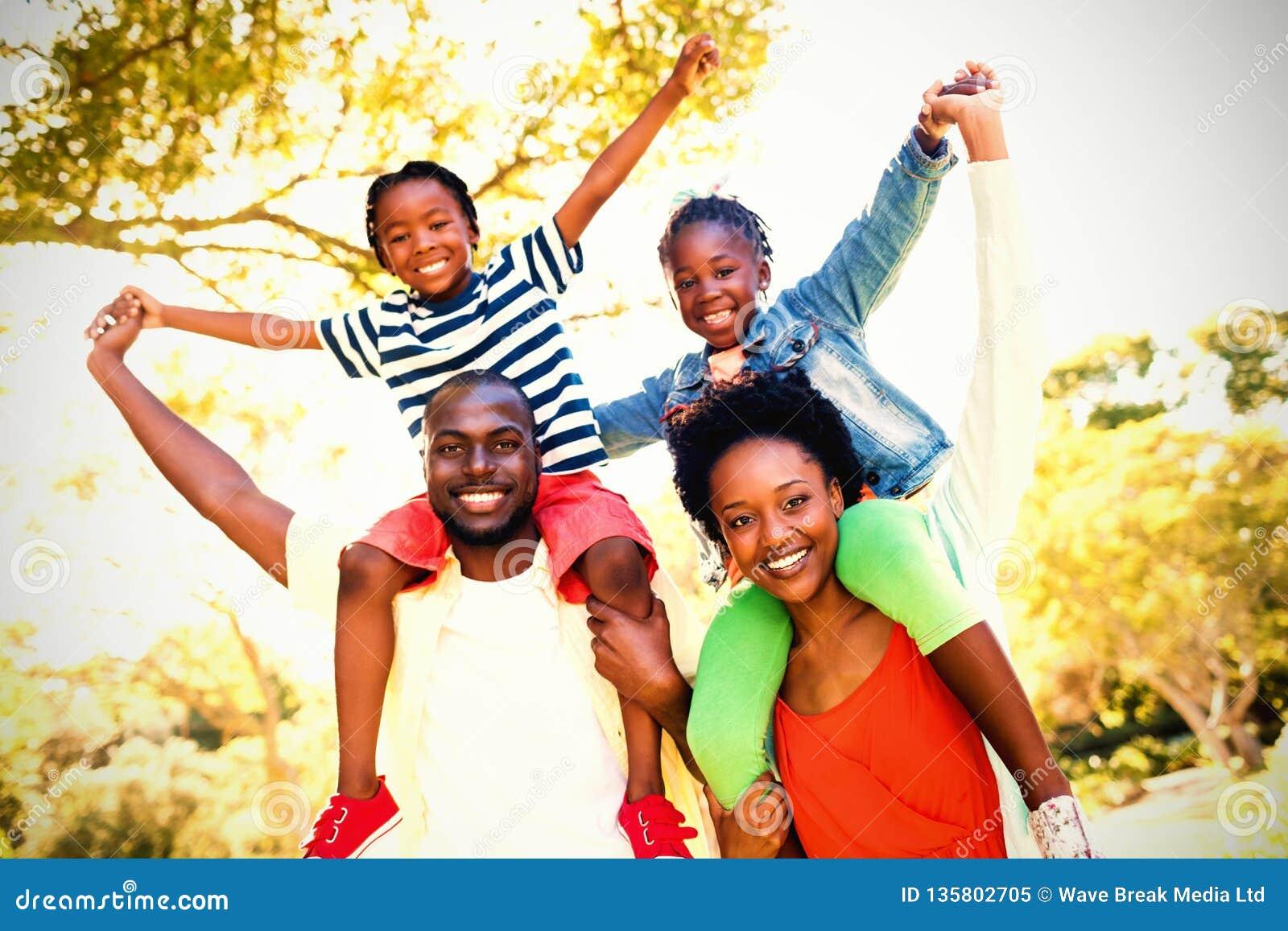 Retrato de la familia feliz que goza en el parque