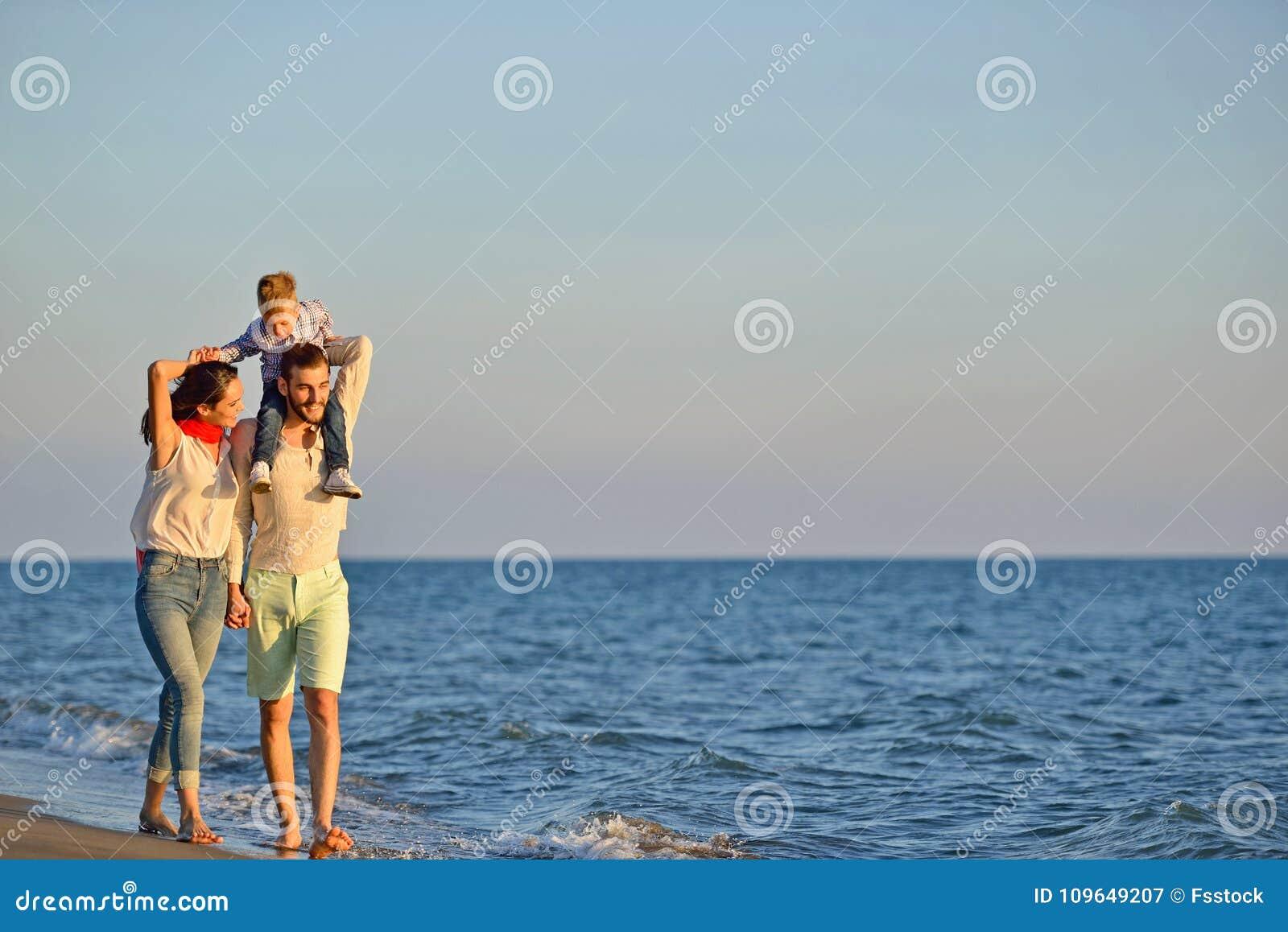 Retrato de la familia feliz y del bebé que disfrutan de puesta del sol en el ocio del verano