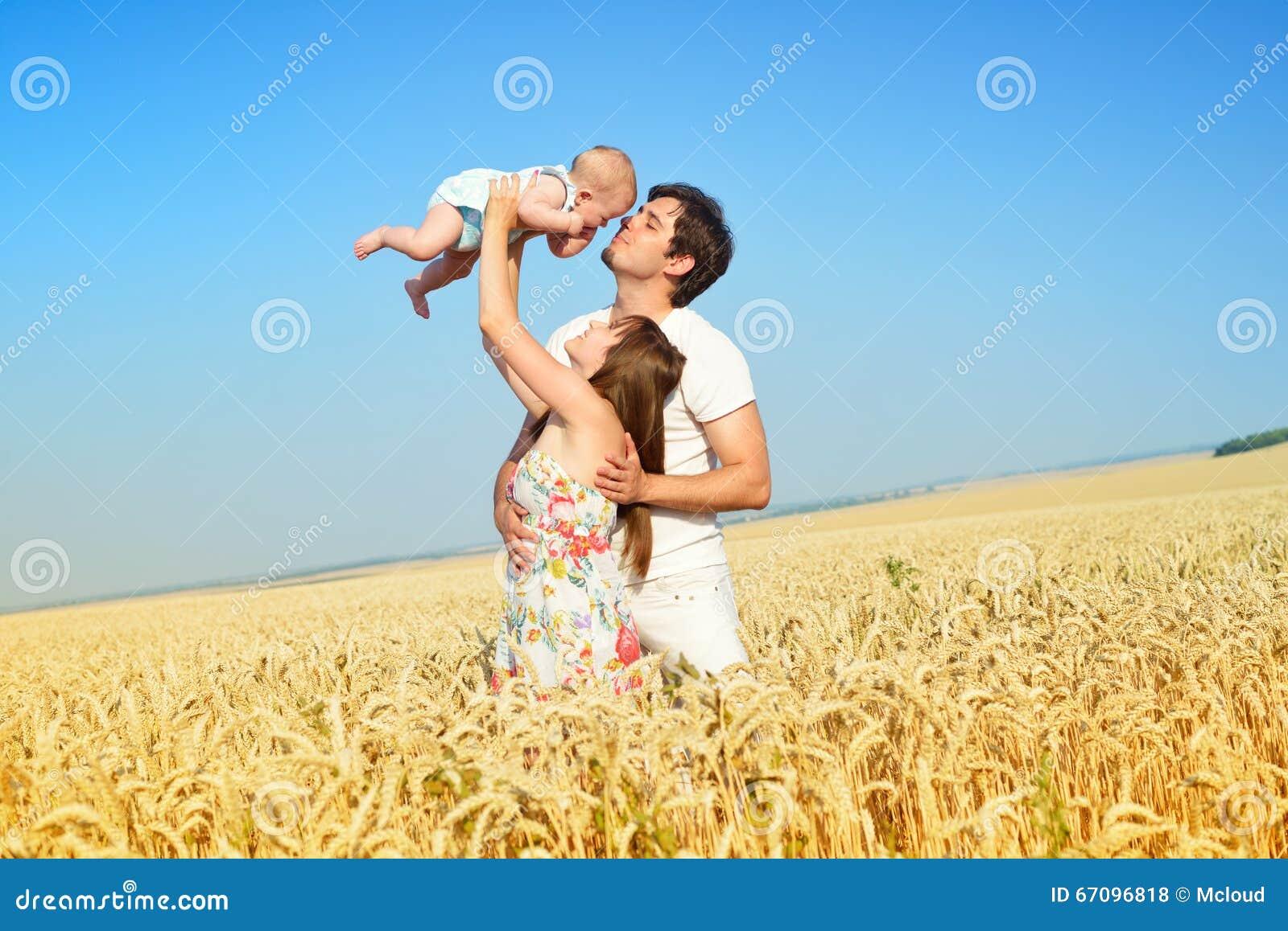 Retrato de la familia Imagen del padre cariñoso feliz, de la madre y de su bebé al aire libre Papá, mamá y niño contra el cielo a