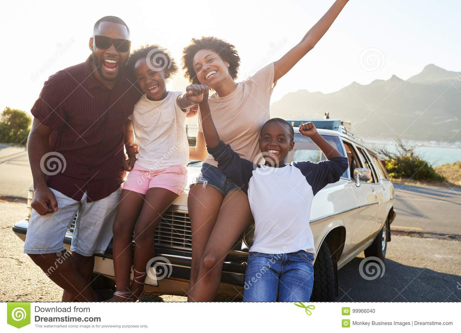 Retrato de la familia que se coloca al lado del coche clásico