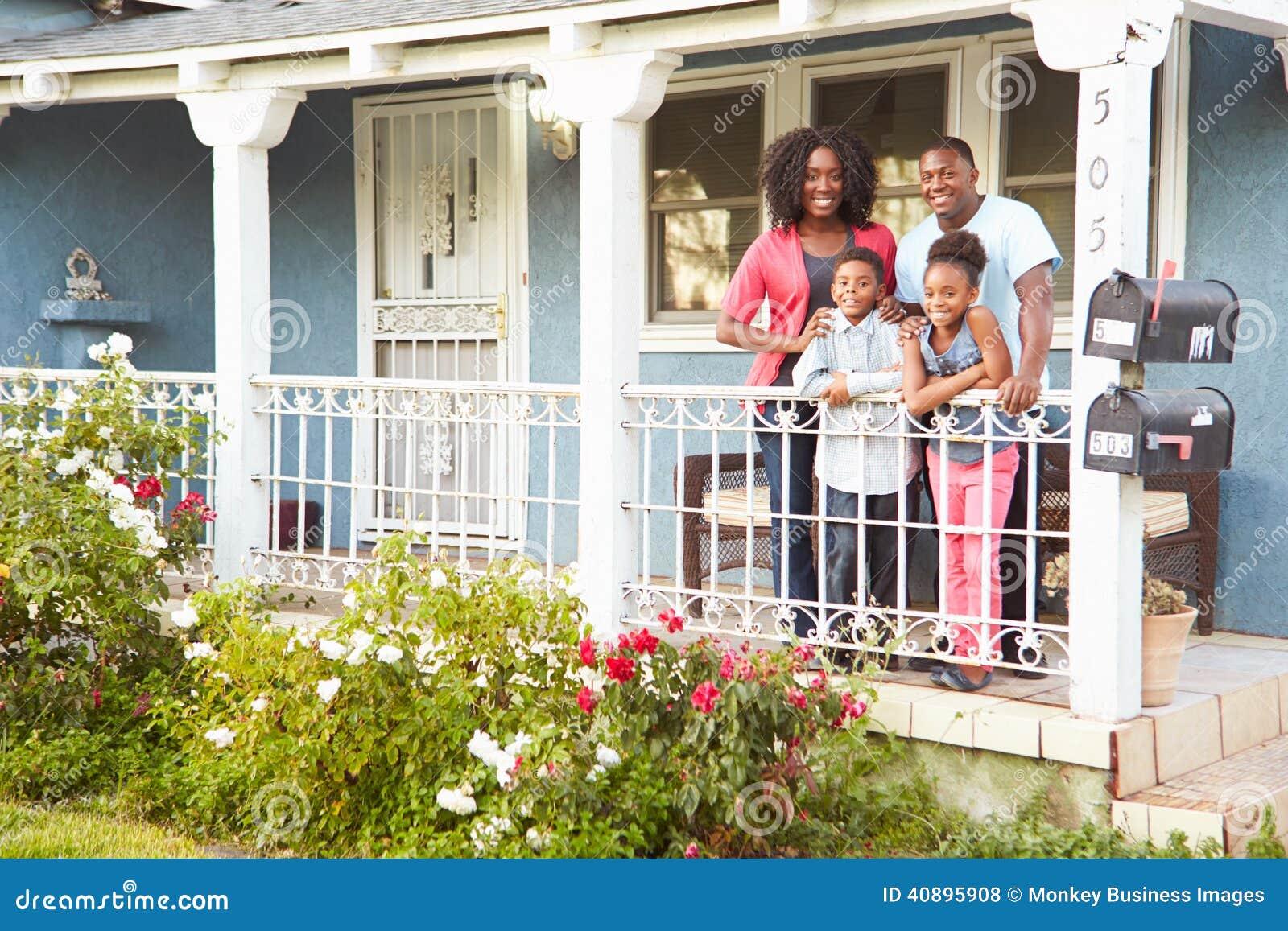 Retrato de la familia que se coloca en el pórtico del hogar suburbano