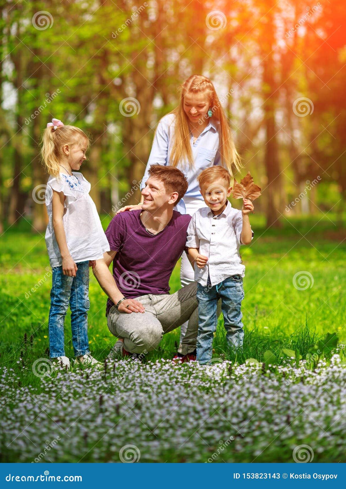 Retrato de la familia que se divierte en parque de florecimiento de la ciudad en el día soleado brillante que pasa feliz su tiemp