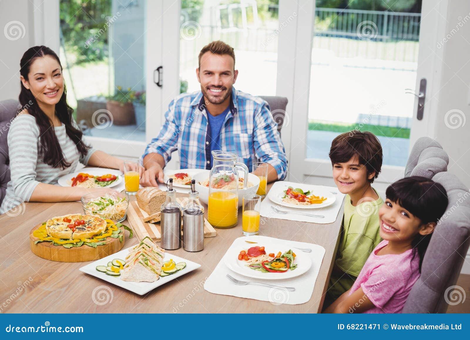 Retrato de la familia sonriente que se sienta en la mesa - El comedor de familia ...