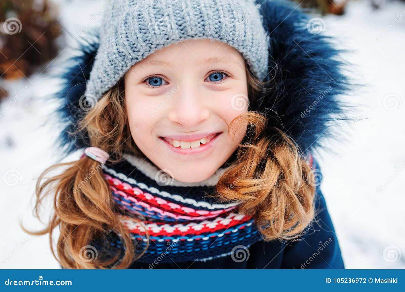 Retrato de la forma de vida del invierno de la muchacha feliz del niño que juega bolas de nieve en el paseo