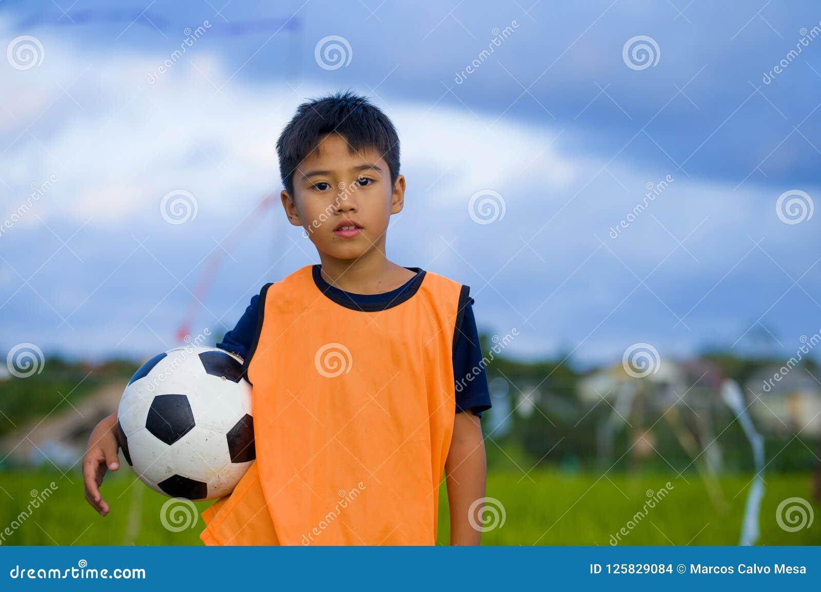 Retrato de la forma de vida del muchacho joven hermoso y feliz que sostiene el balón de fútbol que juega a fútbol al aire libre e