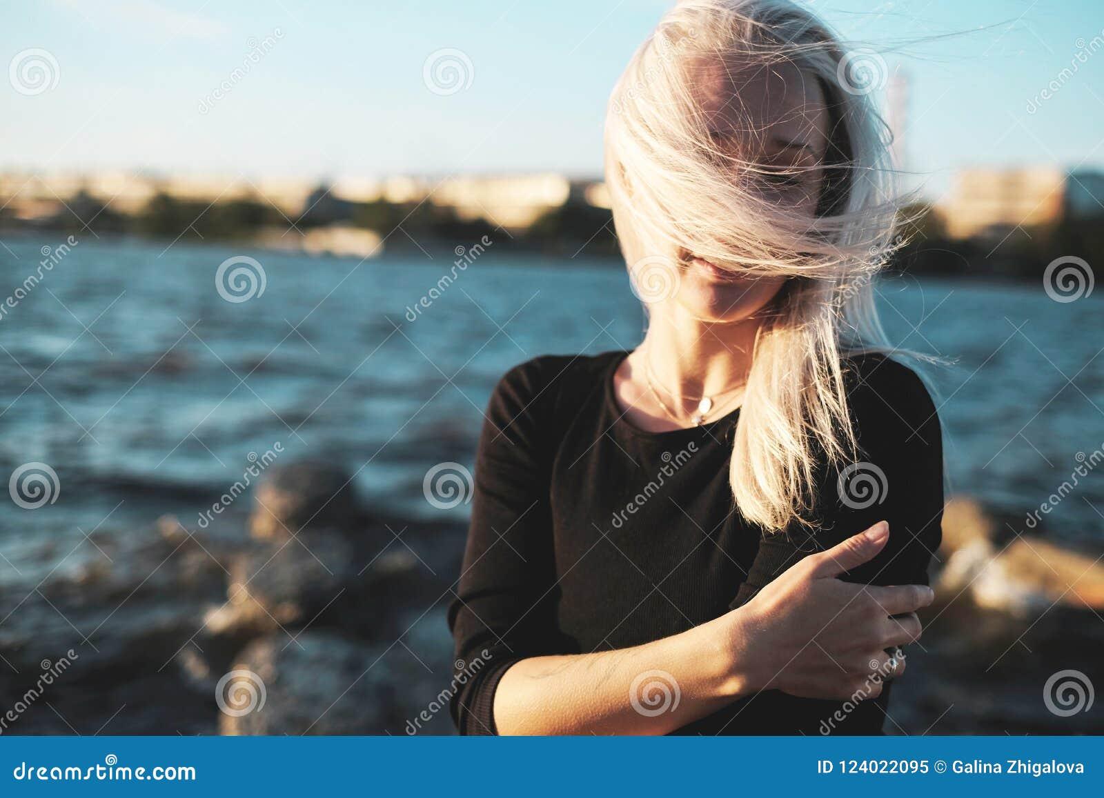 Retrato de la forma de vida de la mujer rubia joven en día ventoso en el mar