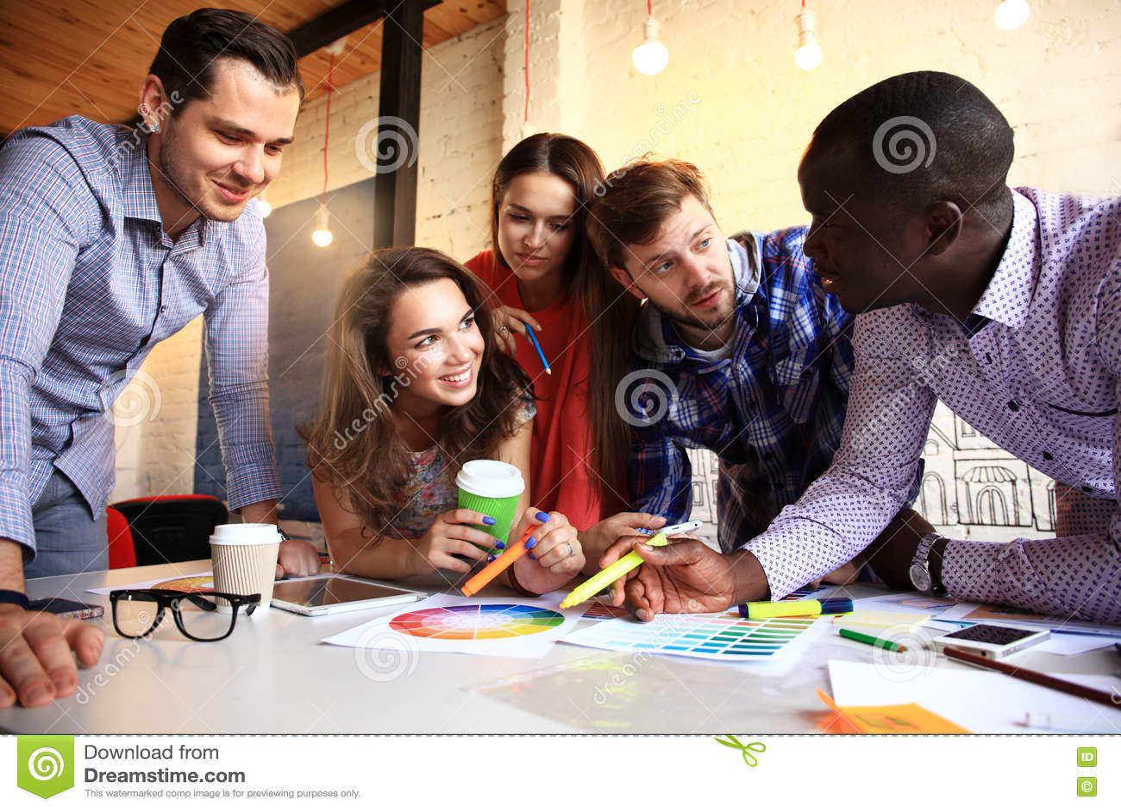 Retrato de la gente joven feliz en una reunión que mira la cámara y la sonrisa Diseñadores jovenes que trabajan junto en a