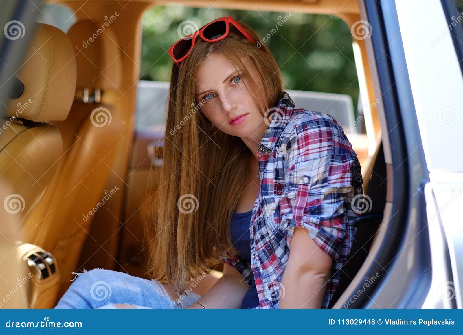 Retrato de la hembra pecosa en un coche