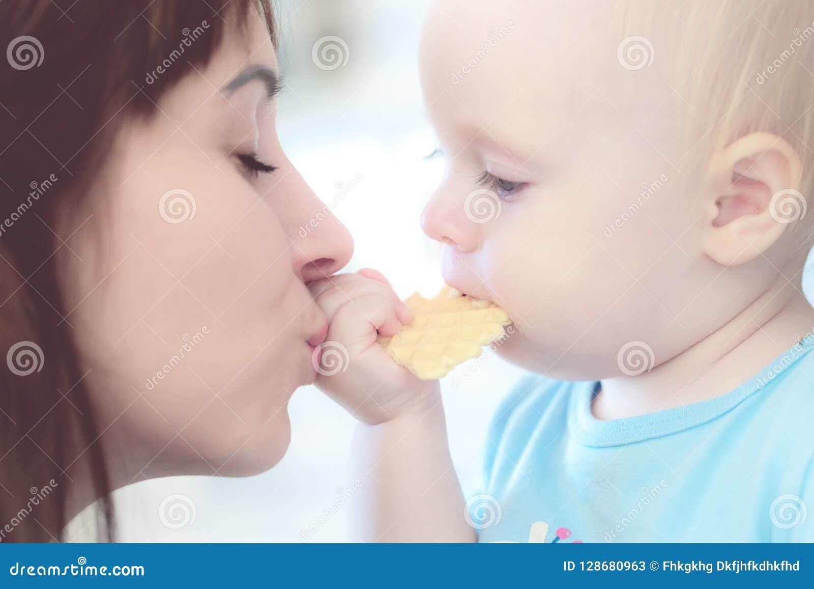 Retrato de la madre hermosa que besa a su muchacha del niño