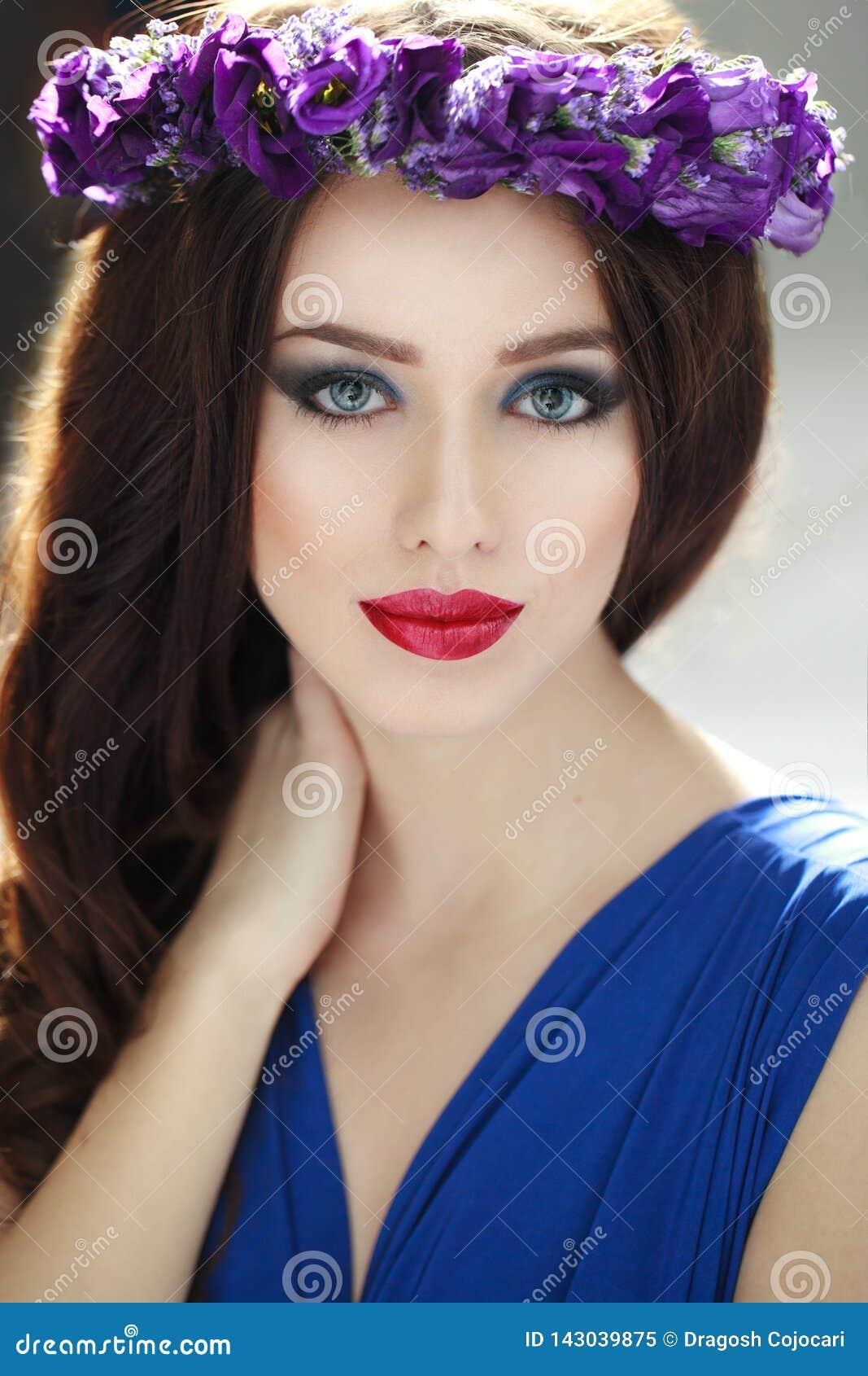 Retrato de la moda de una mujer joven de la morenita de la belleza con la corona de la flor del purpple El peinado y perfectos co