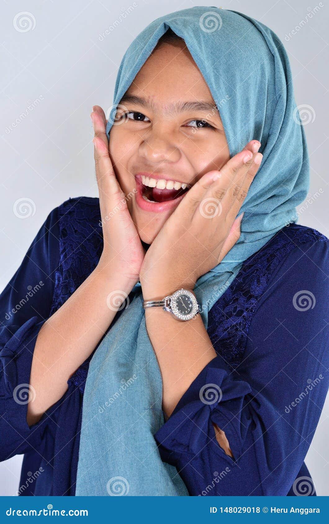 Retrato de la muchacha asiática feliz que lleva el hijab azul que sonríe en usted y que toca su mejilla
