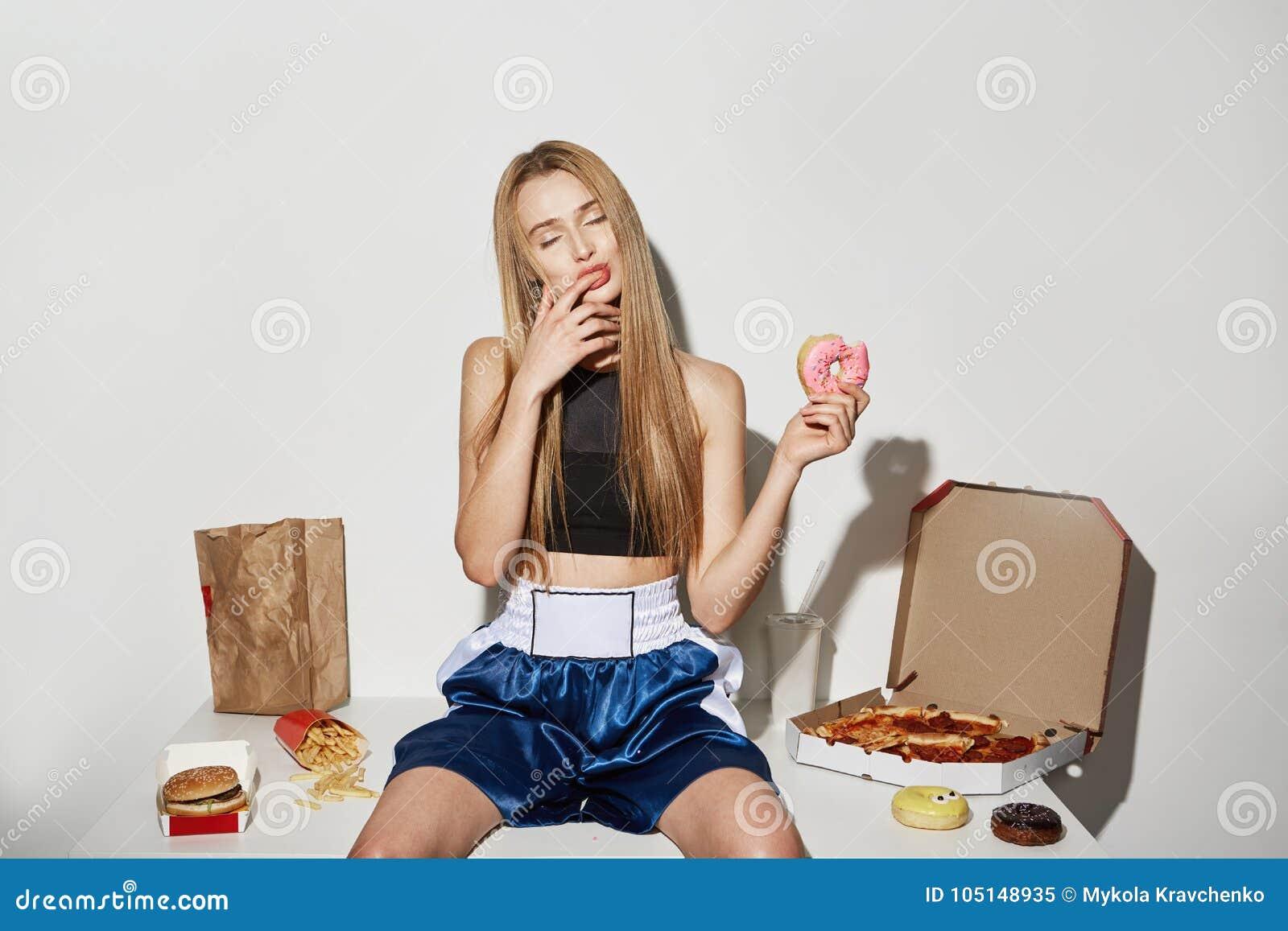 Retrato de la muchacha atractiva con el pelo rubio en top del deporte y de los pantalones cortos que se sientan en la tabla con c