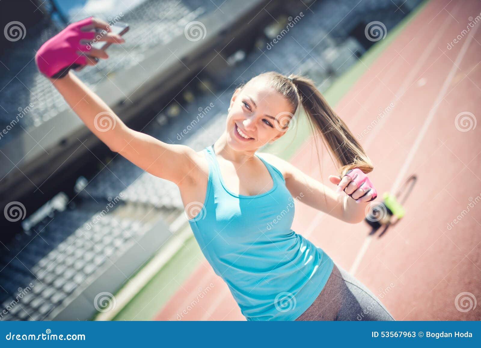 Retrato de la muchacha bonita que sonríe y que toma un selfie mientras que entrena Mujer hermosa que toma imágenes de sí misma Me