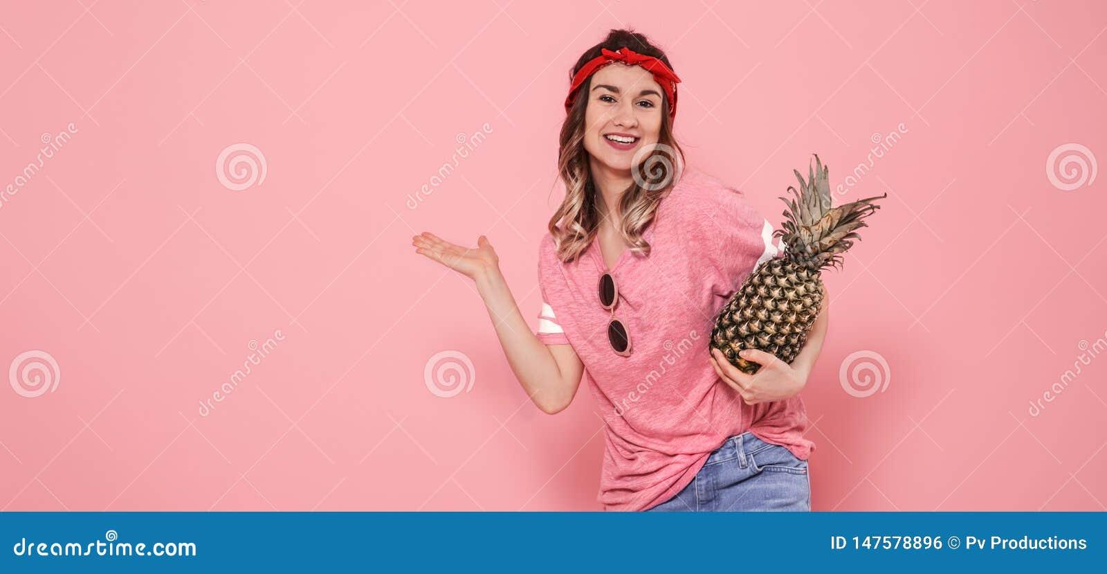 Retrato de la muchacha del inconformista en vidrios y pi?a en fondo rosado