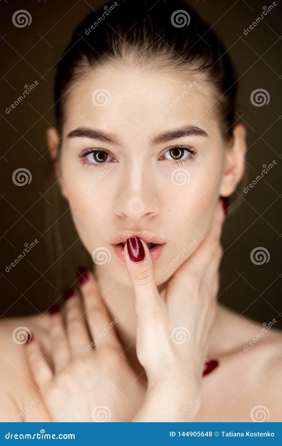 Retrato de la muchacha encantadora joven con el maquillaje natural que lleva a cabo sus manos en su cara