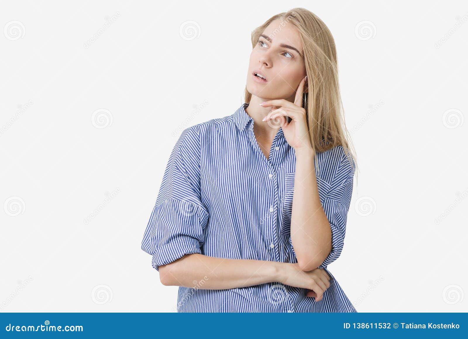 Retrato de la muchacha europea rubia joven que lleva la camisa rayada azul que piensa en algo sobre el fondo blanco