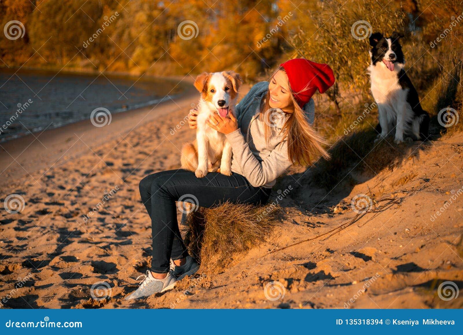 Retrato de la muchacha feliz con el perro divertido del border collie dos en la playa en la playa bosque amarillo del otoño en fo
