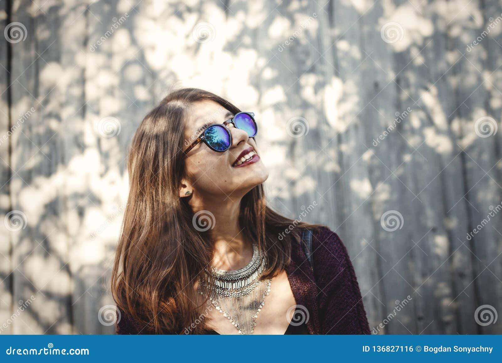 Retrato de la muchacha feliz del boho en equipo y gafas de sol frescos que sonríe en luz del sol Muchacha elegante del inconformi