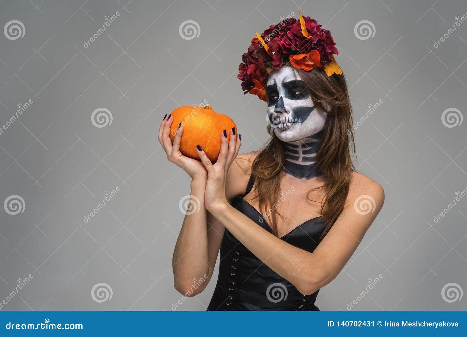 Retrato de la muchacha hermosa joven con el maquillaje esquel?tico temeroso de Halloween con una guirnalda Katrina Calavera hecho
