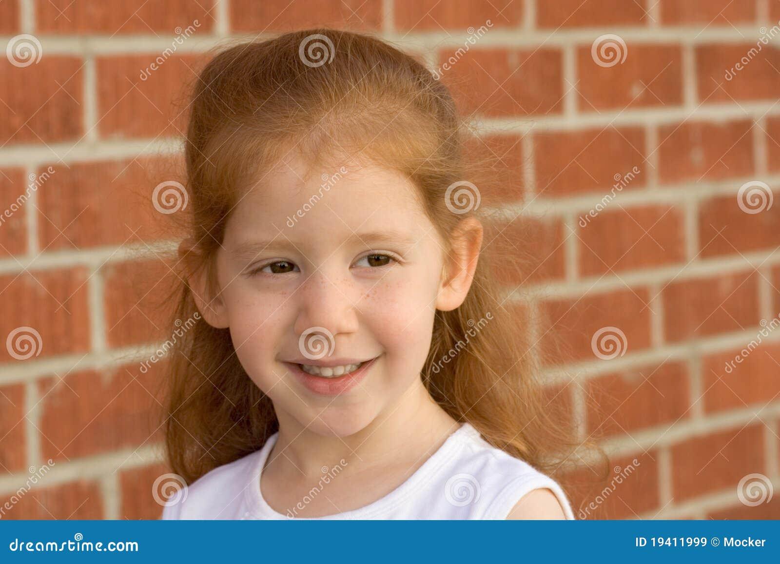 Retrato de la muchacha joven del cabrito del redhead por la pared de ladrillo