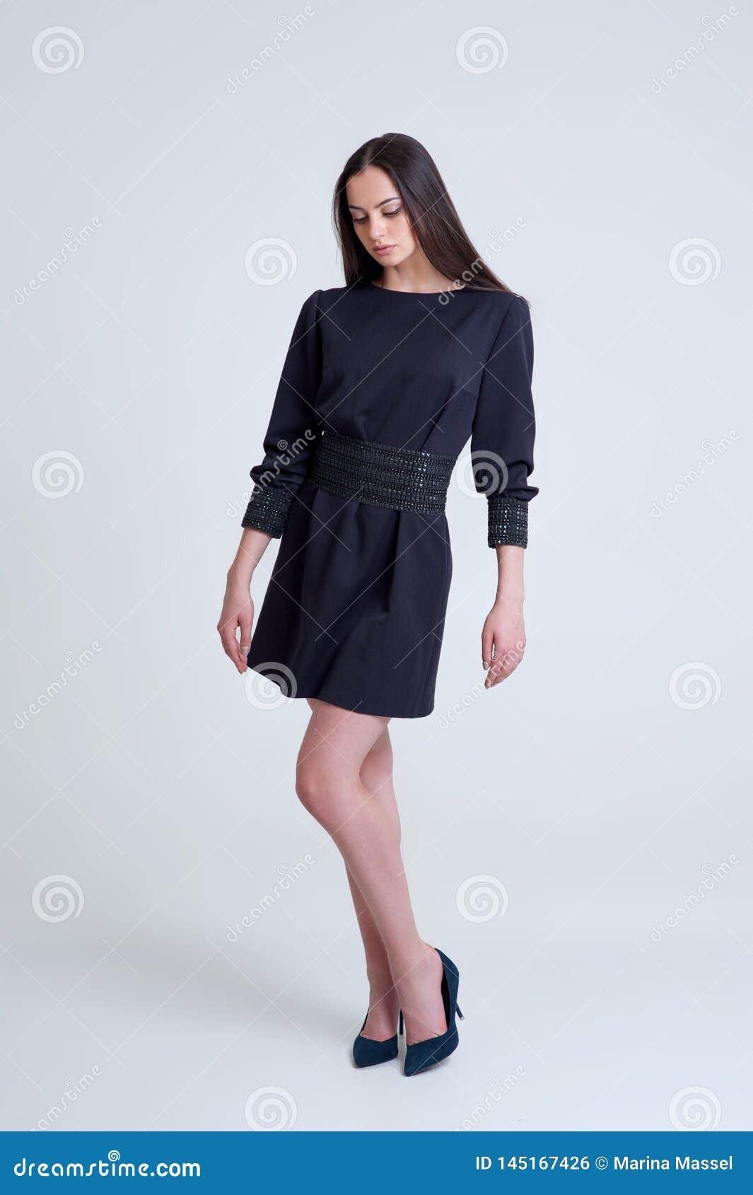 Retrato de la muchacha morena hermosa en vestido azul corto
