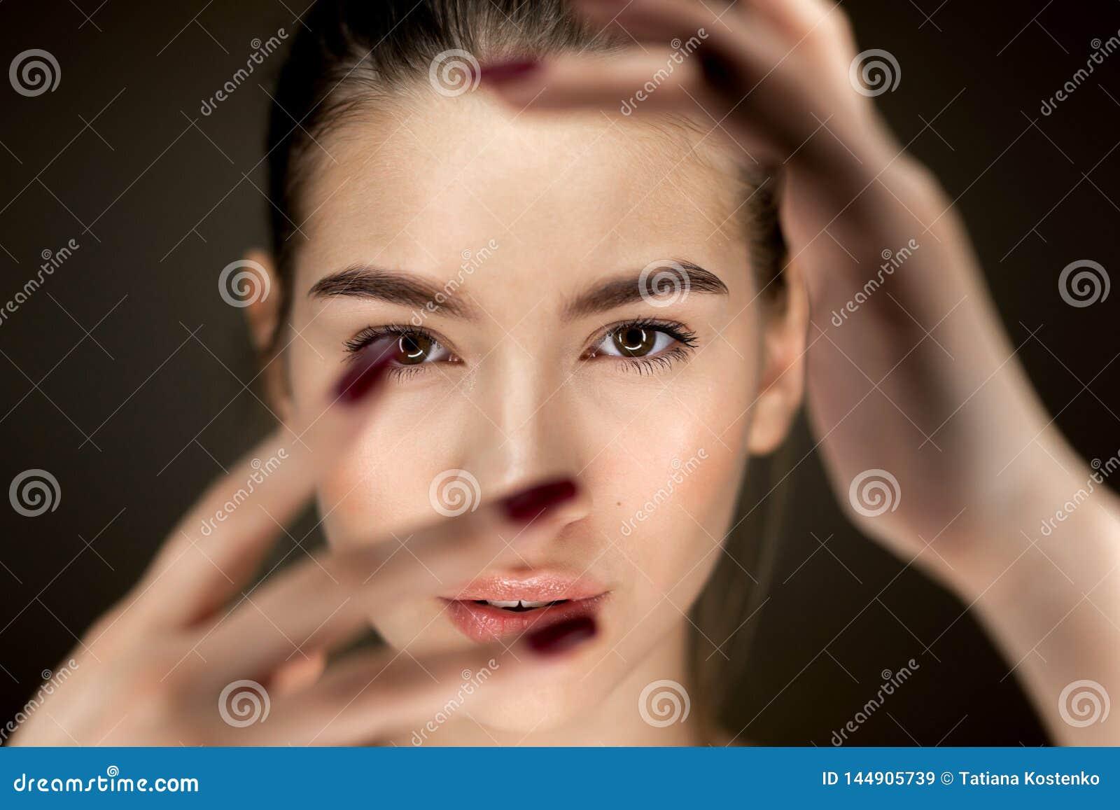 Retrato de la muchacha morena hermosa joven con el maquillaje natural que se sostiene los fingeres delante de su cara