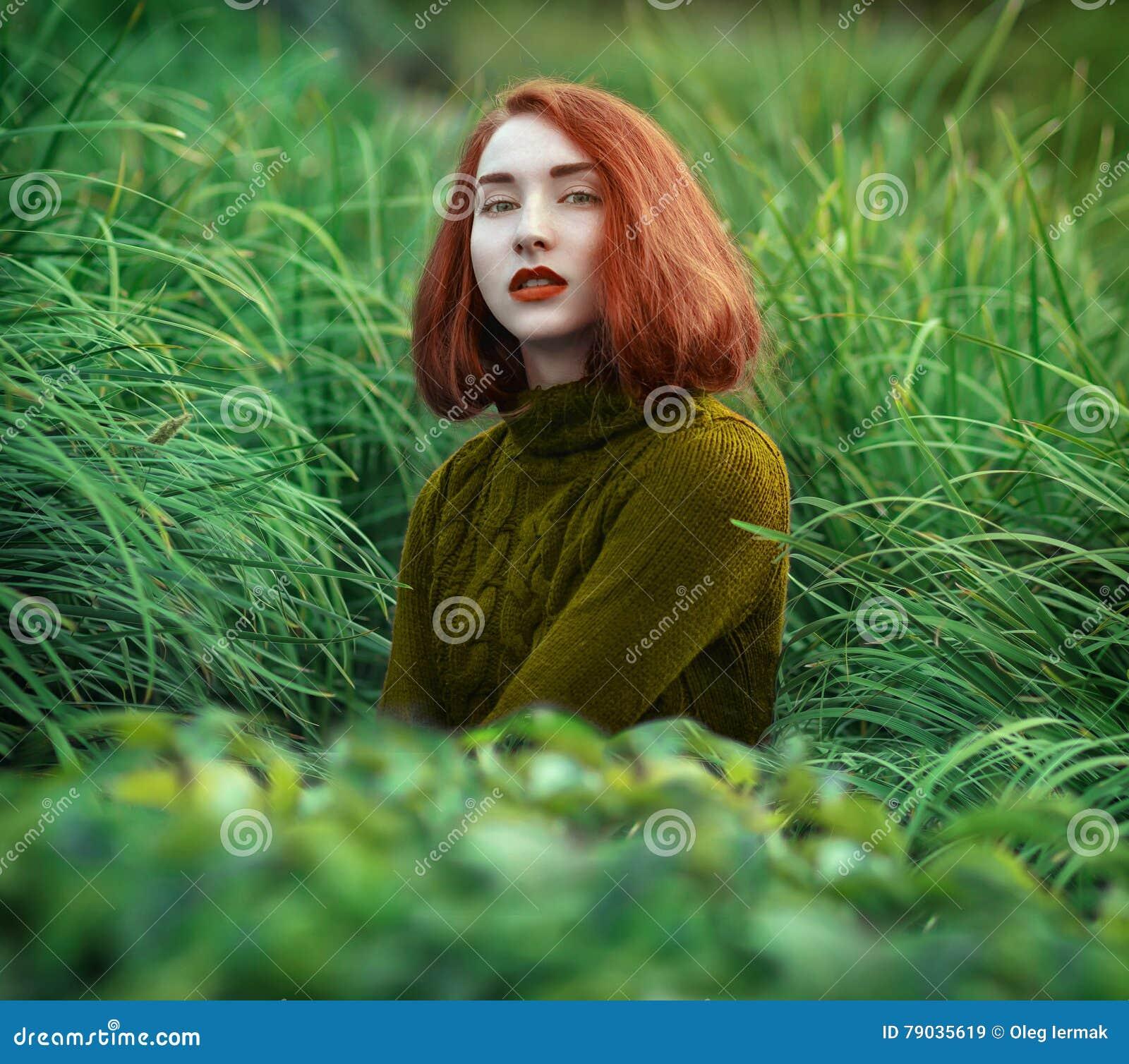Retrato de la muchacha pelirroja hermosa en hierba alta en un interruptor caliente