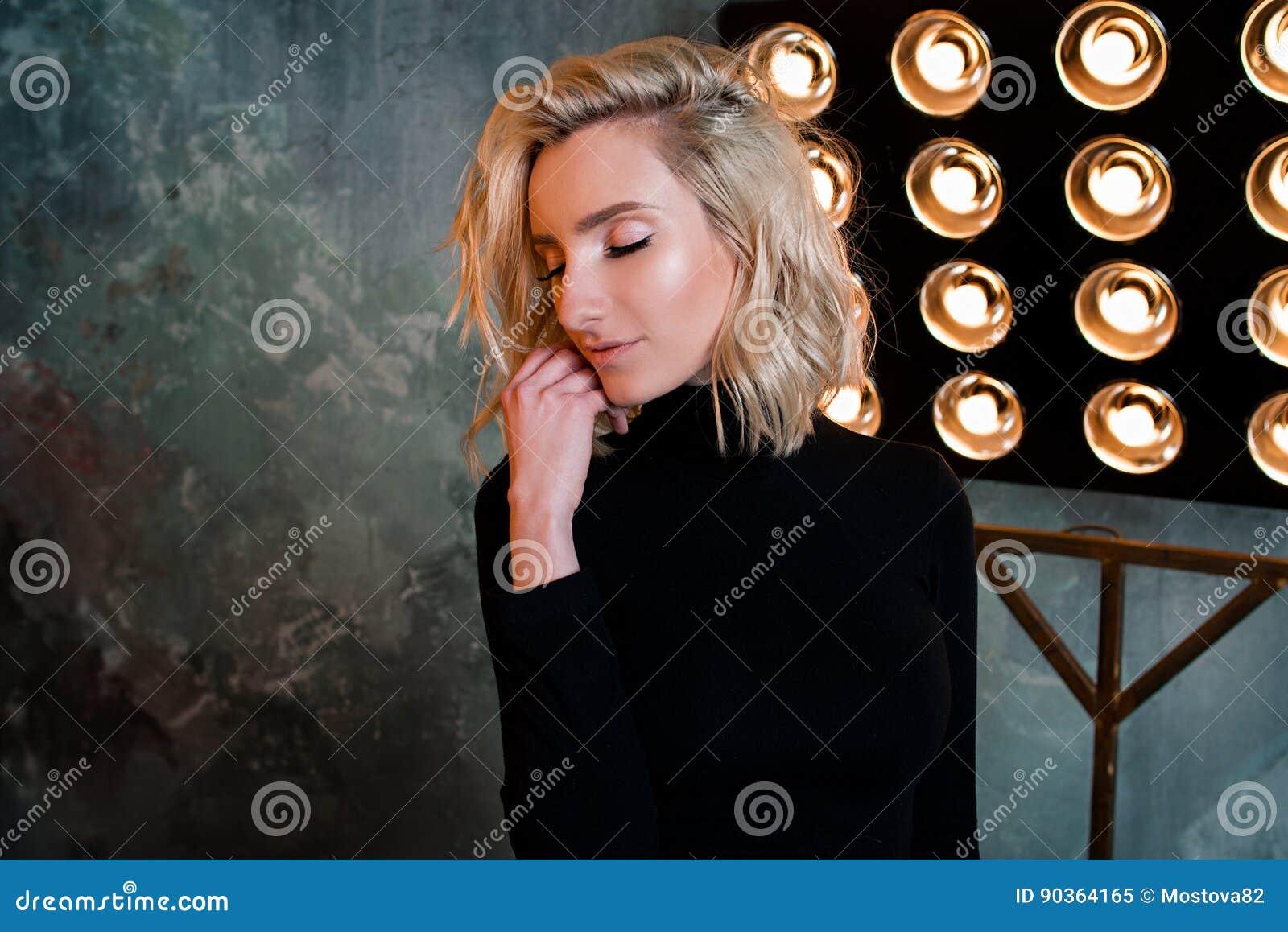 Retrato de la muchacha rizada atractiva hermosa elegante joven en suéter negro en la etapa