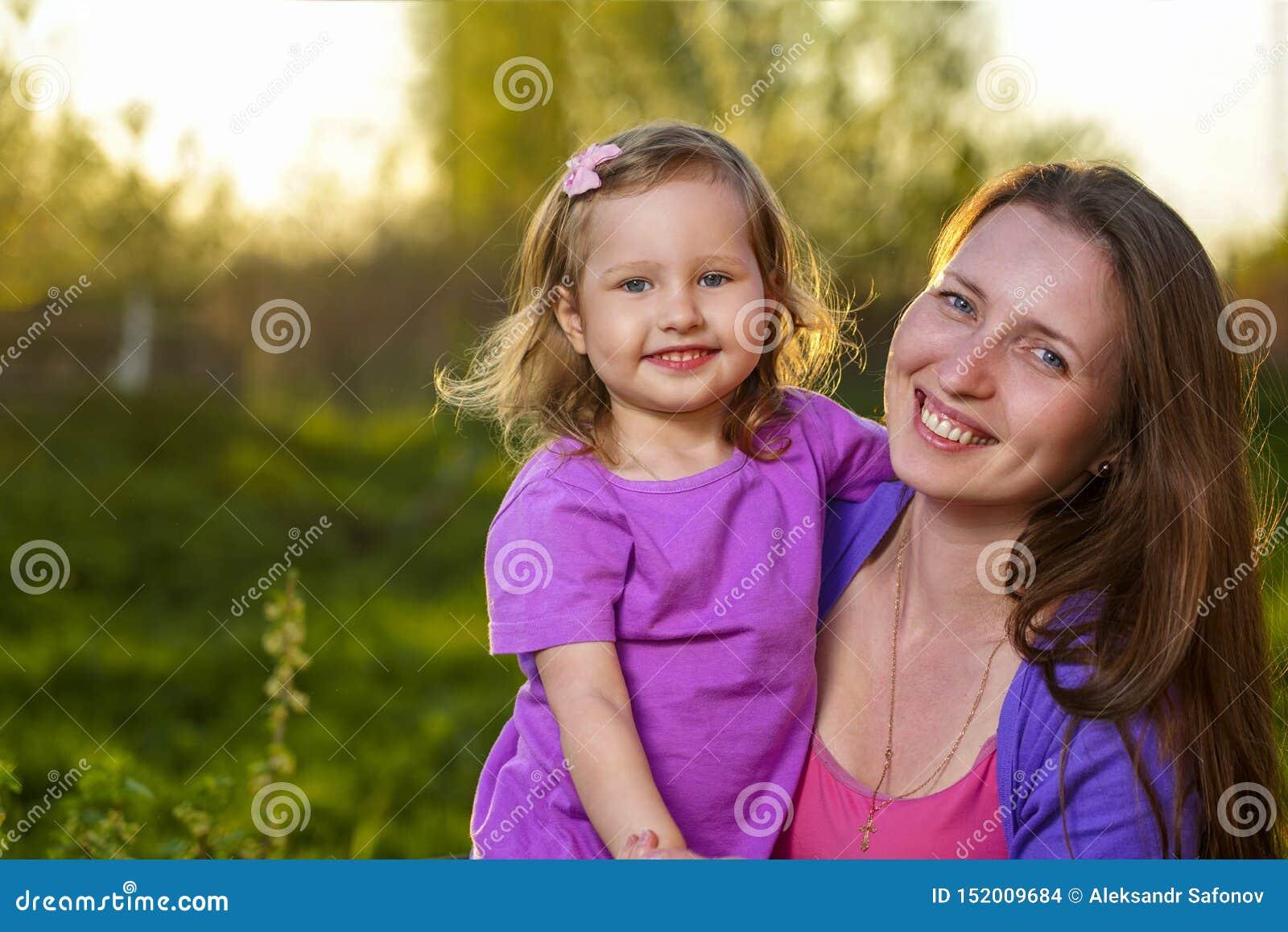 Retrato de la muchacha rubia atractiva y su de la madre que abrazan mirando la cámara y sonriendo al aire libre