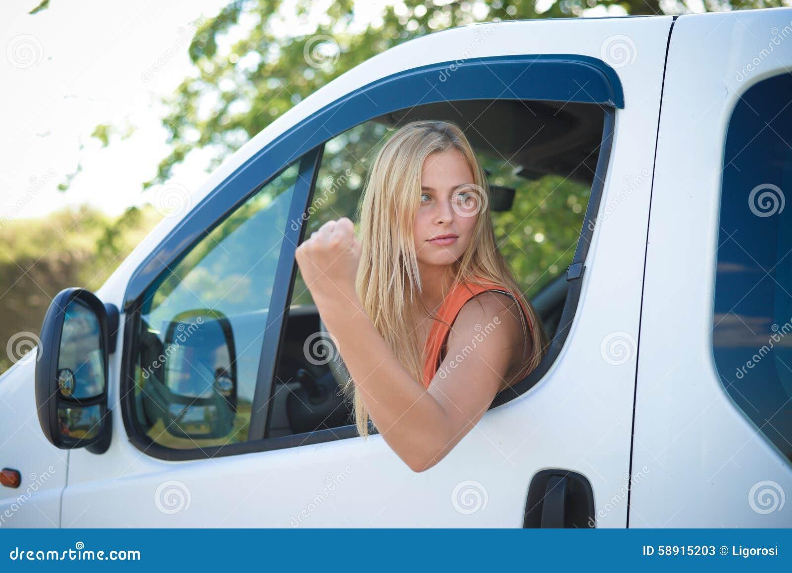 Retrato de la muchacha rubia enojada en la demostración blanca del coche