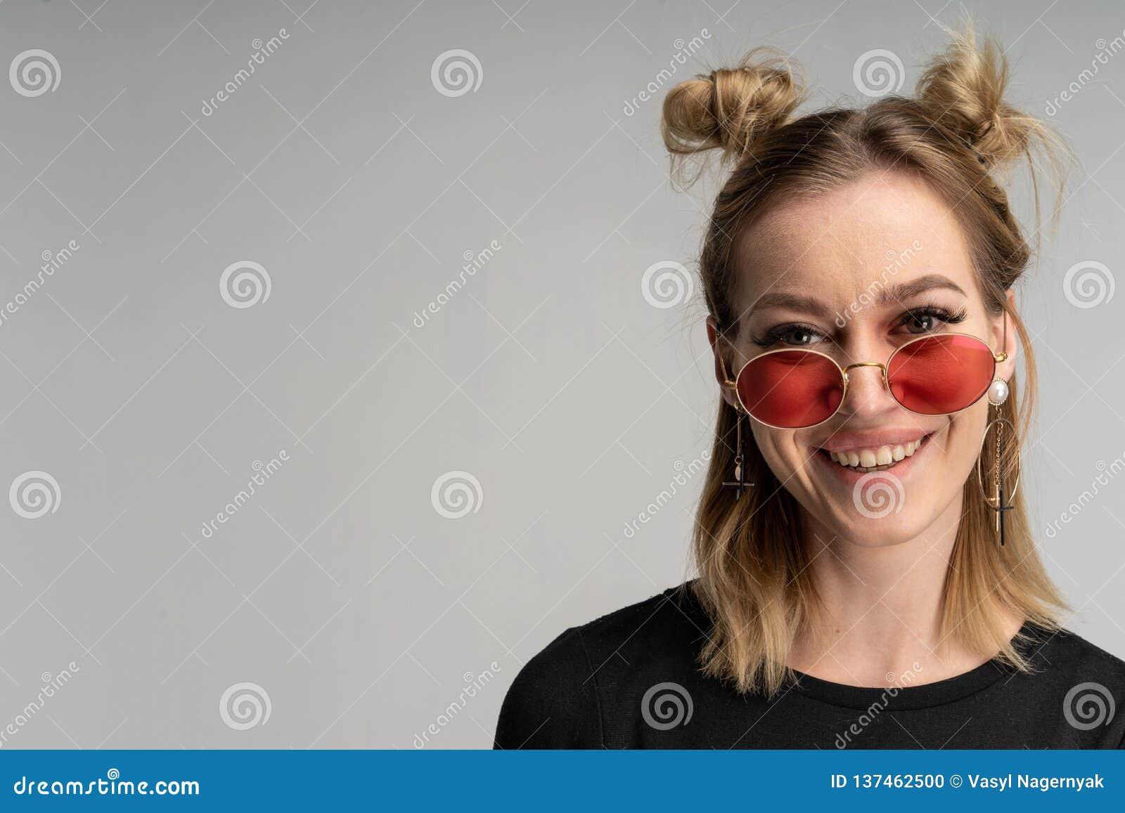Retrato de la muchacha rubia joven hermosa en vestido negro y gafas de sol redondas