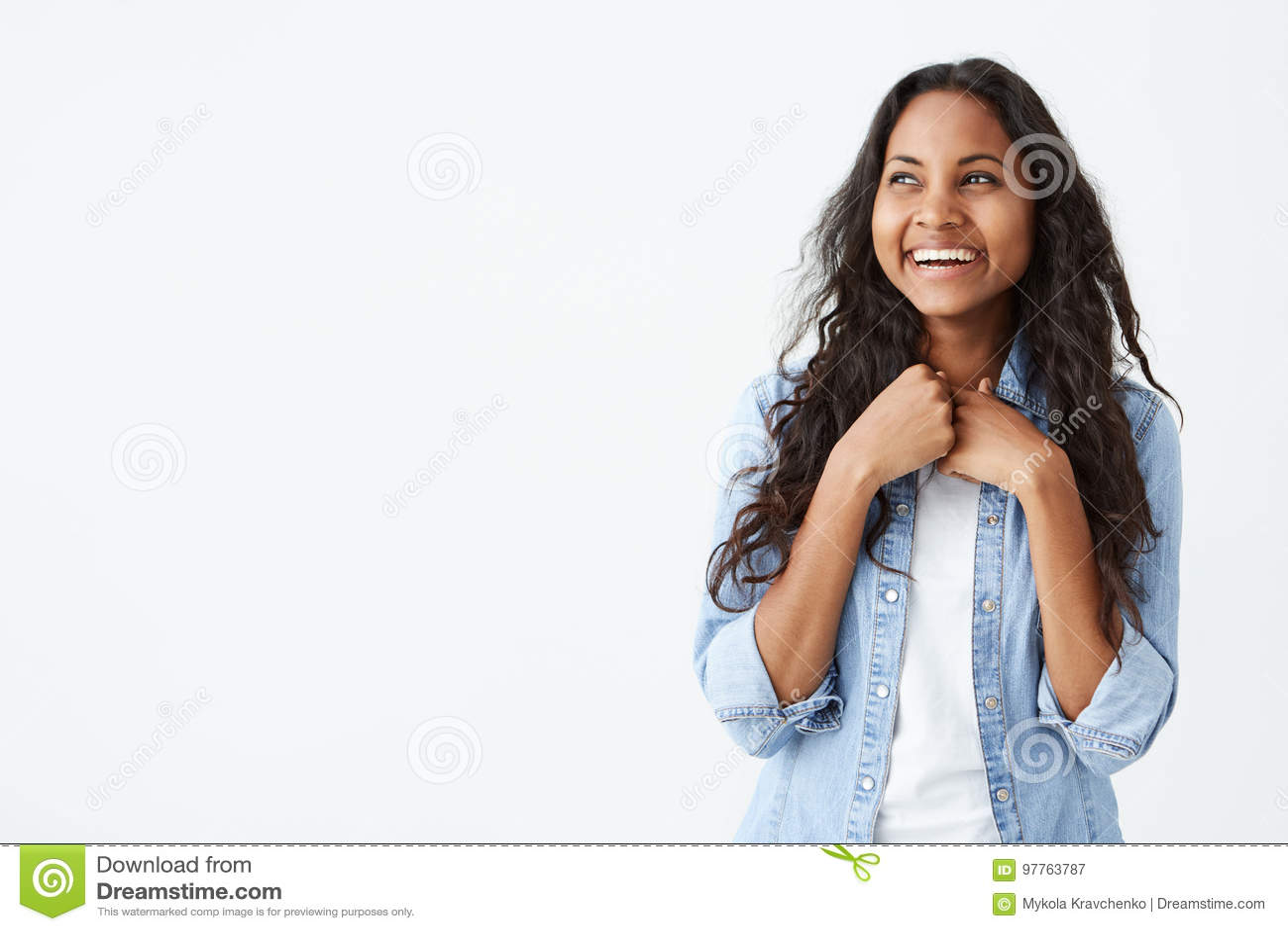 Retrato de la mujer afroamericana carismática y encantadora con el pelo ondulado largo que lleva la camisa elegante del dril de a