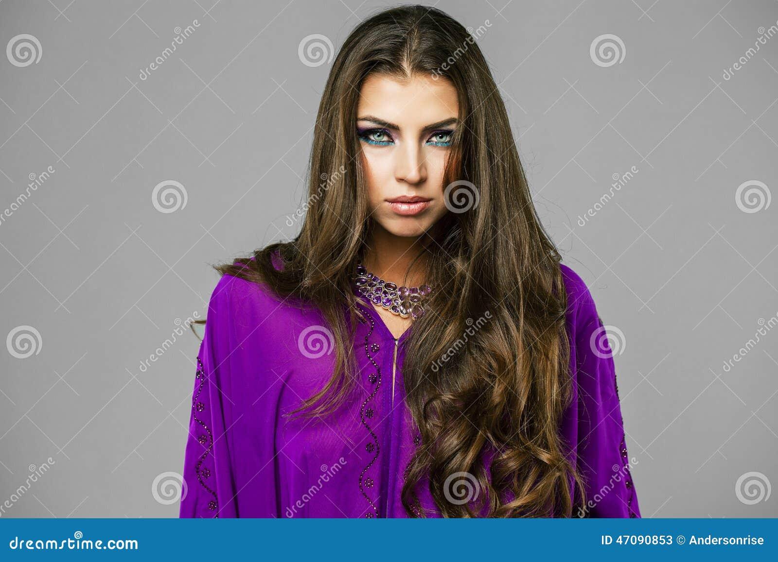 Retrato de la mujer atractiva joven en árabe púrpura de la túnica