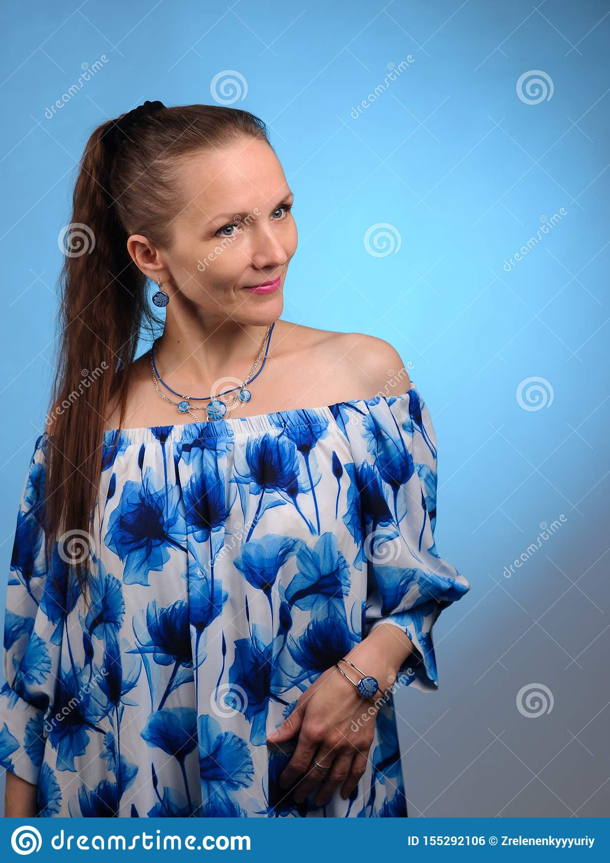 Retrato de la mujer bonita en vestido azul sobre fondo azul