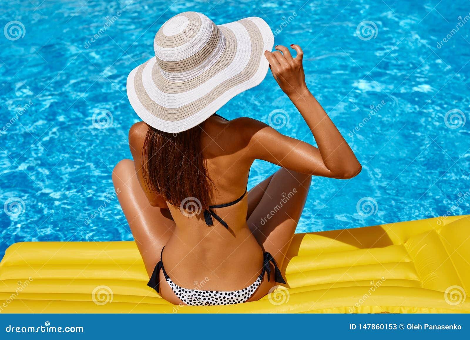 Retrato de la mujer bronceada hermosa que se relaja en bikini y sombrero en piscina Manicura roja polaca del gel D?a de verano y