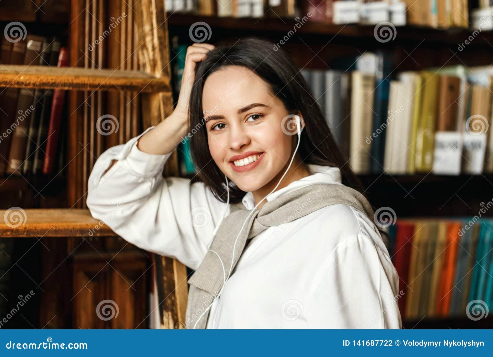 Retrato de la mujer cerca de los estantes