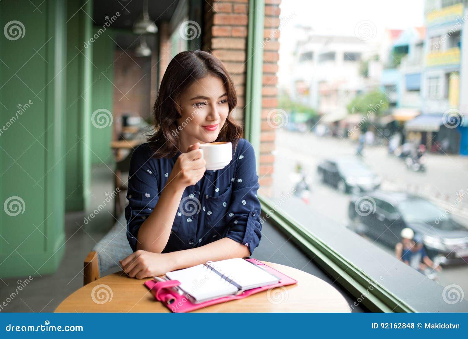 Retrato de la mujer de negocios joven feliz con la taza en drinkin de las manos