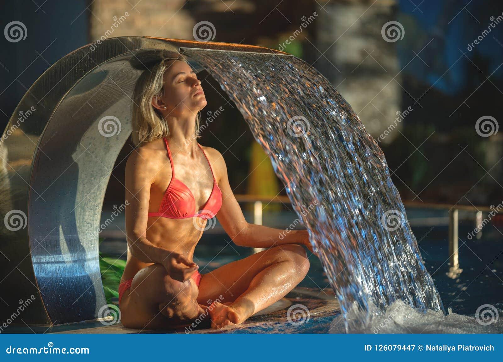 Retrato de la mujer delgada deportiva hermosa que se relaja en balneario de la piscina