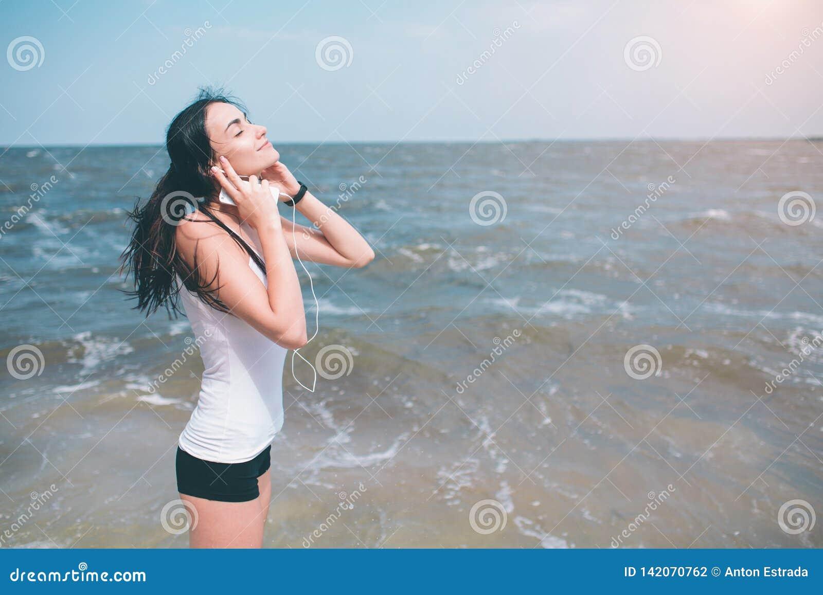 Retrato de la mujer deportiva joven en los auriculares que se relajan mientras que se sienta cerca del océano en el verano, el es