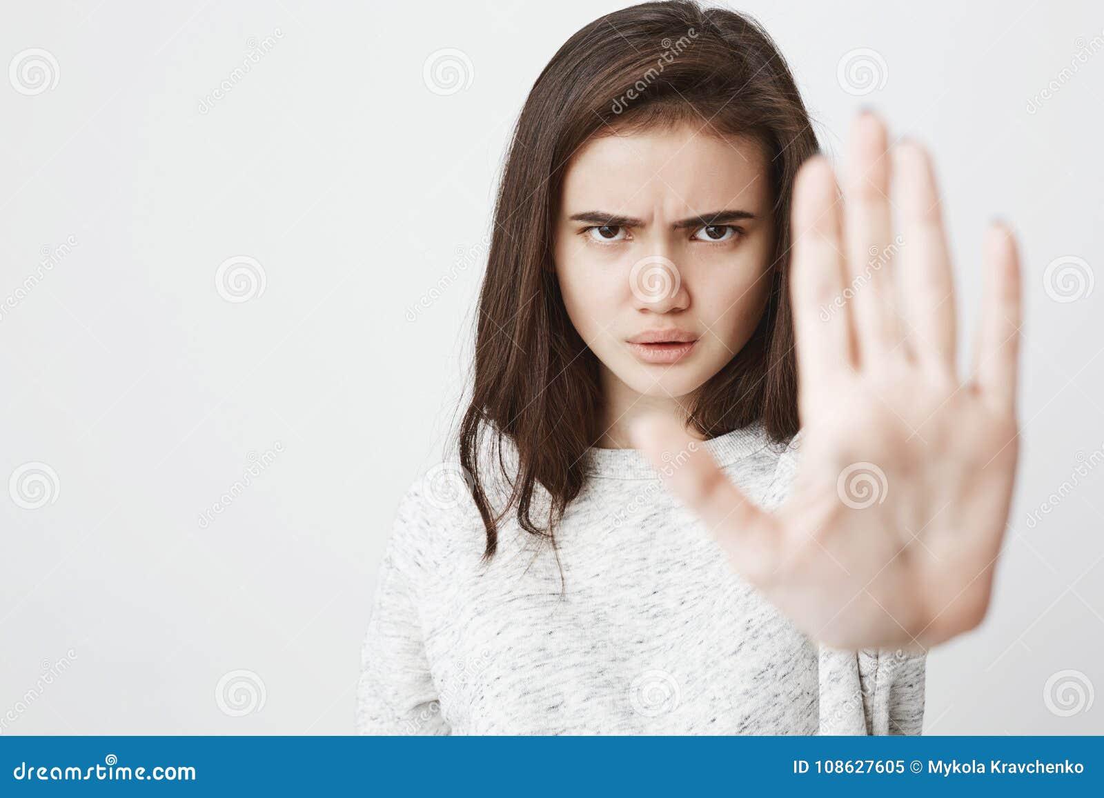 Retrato de la mujer europea hermosa con la expresión seria y enojada que estira una mano en gesto del control o de la parada, enc