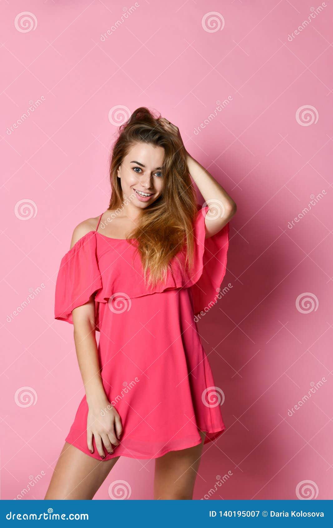 Retrato de la mujer hermosa feliz en el vestido rosado que presenta en estudio