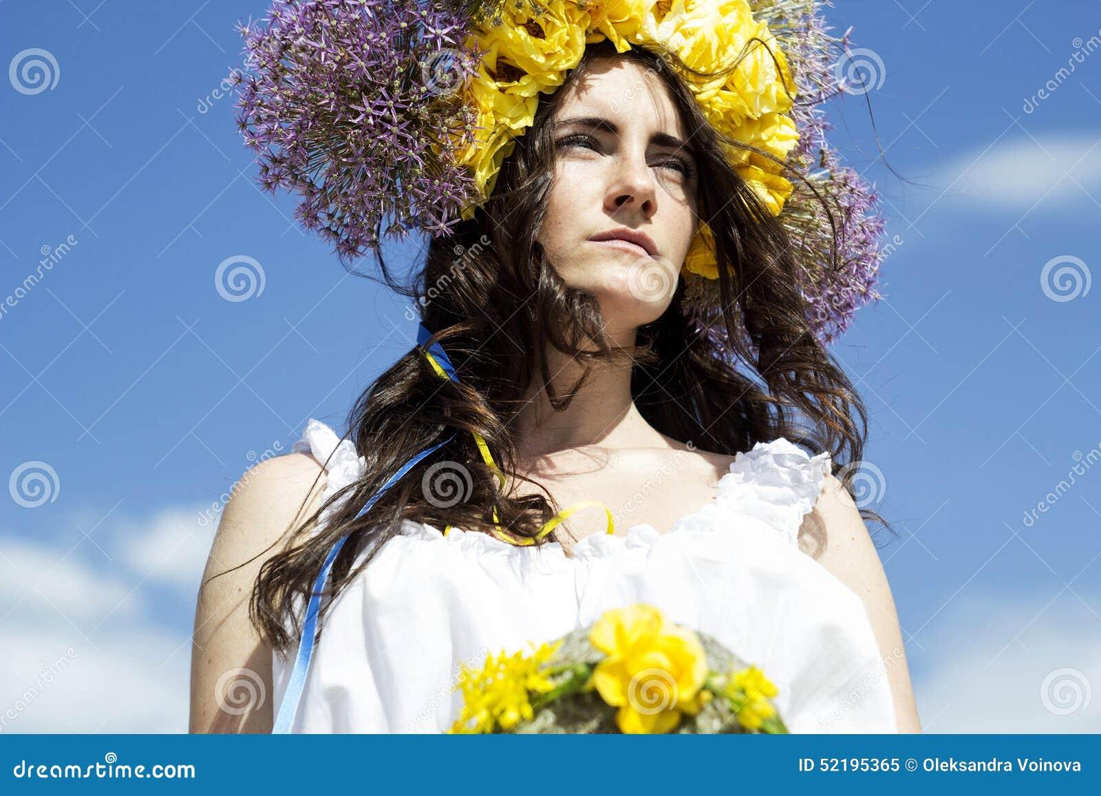 Retrato de la mujer hermosa joven con el anillo de flores en la cabeza