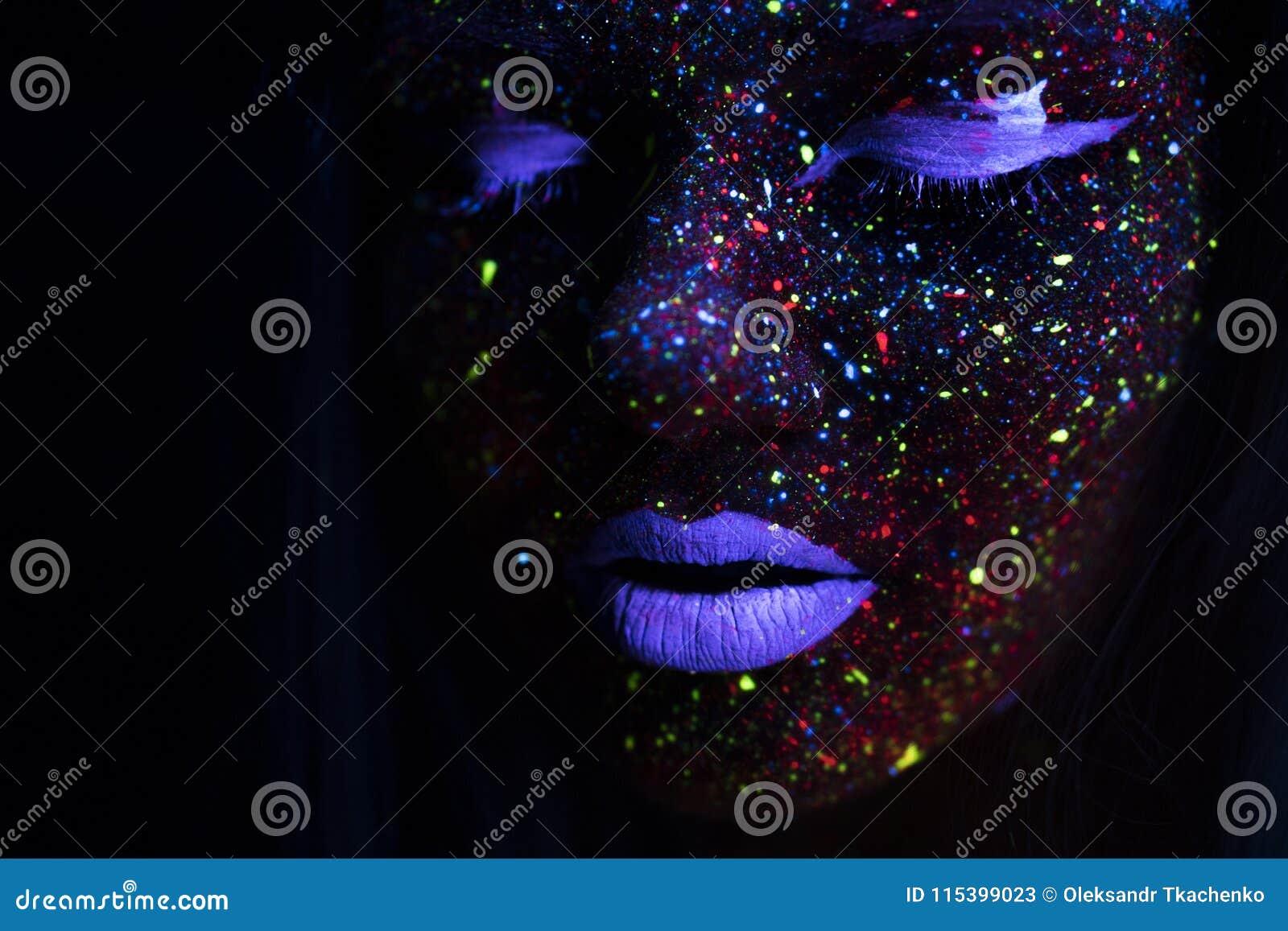 Retrato de la mujer hermosa de la moda en la luz de neón del uF Girl modelo con el maquillaje psicodélico creativo fluorescente,