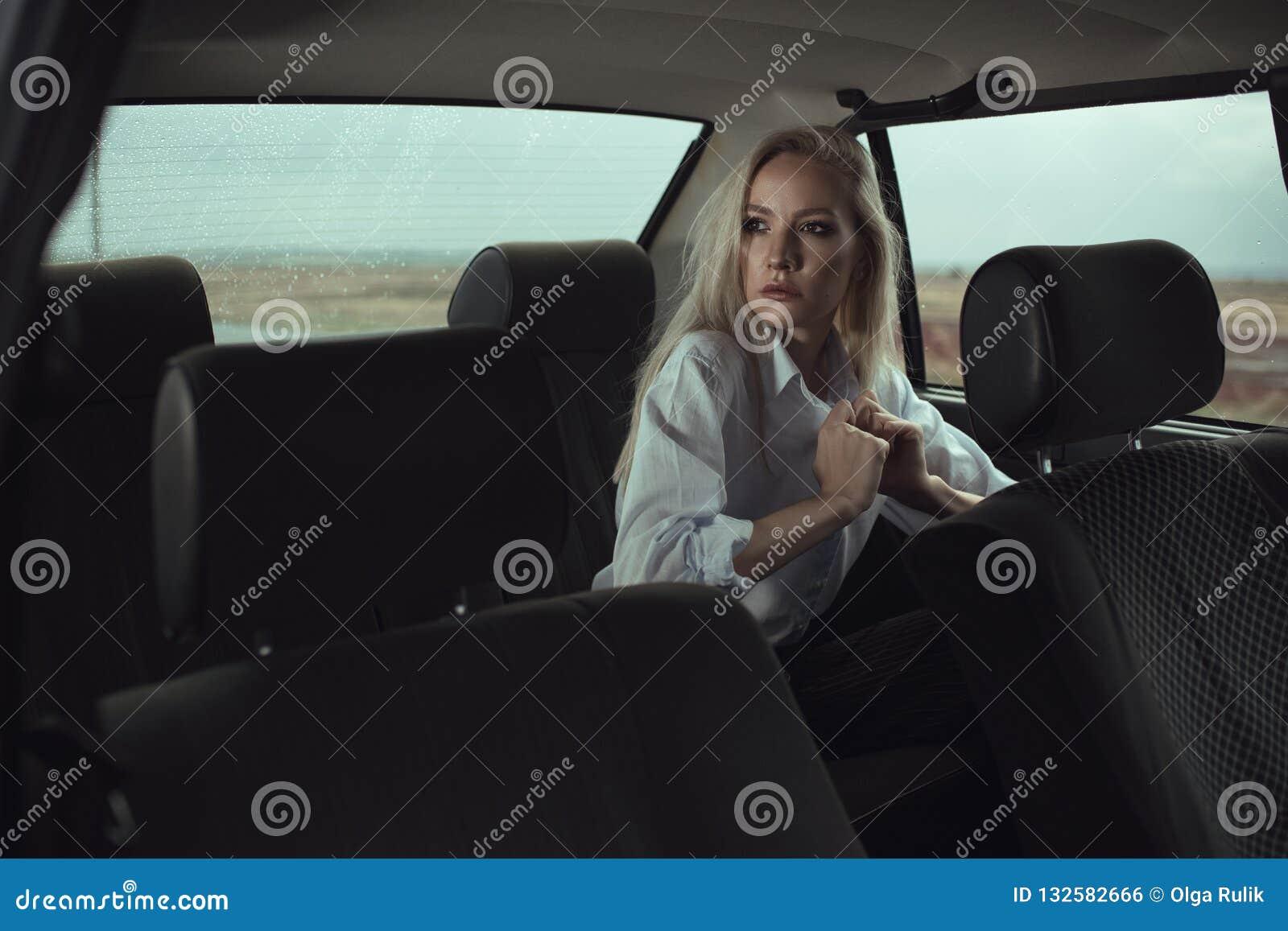 Retrato de la mujer hermosa que se sienta en el asiento trasero del coche viejo y que mira la ventana cuidadosamente